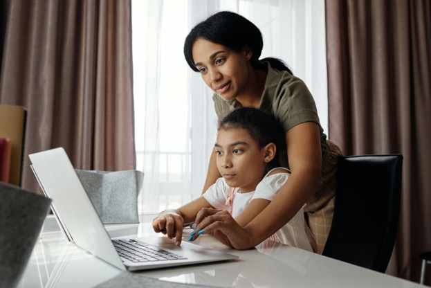 A person and a child looking at a computer  Description automatically generated with medium confidence