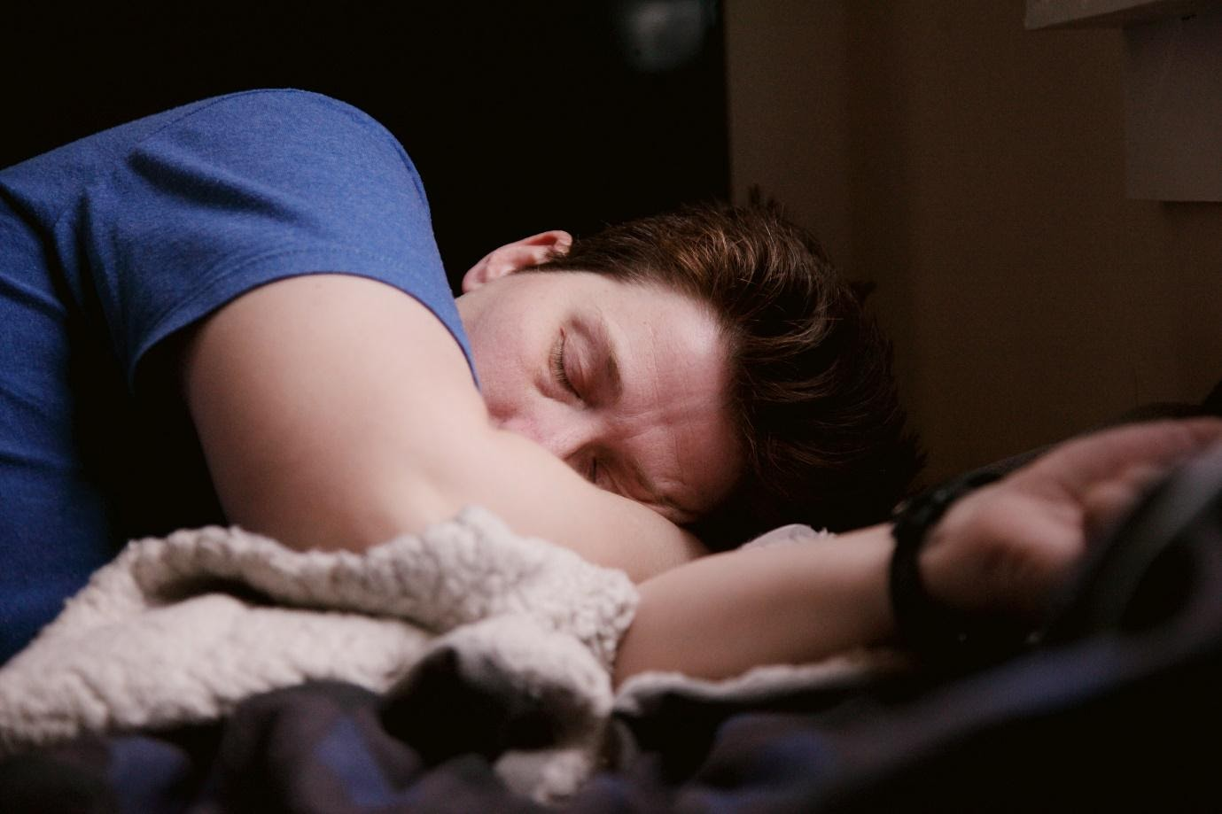 A person sleeping on a bed  Description automatically generated with medium confidence